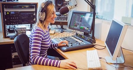 weiblicher radiomoderator der ueber mikrofon sendet