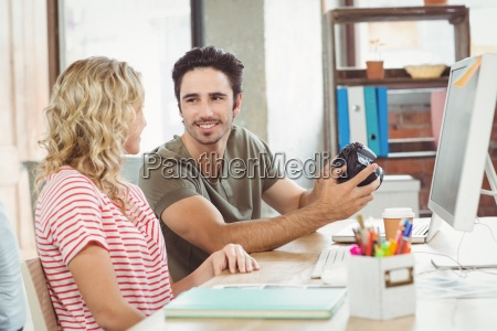 businessman holding digital camera while discussing