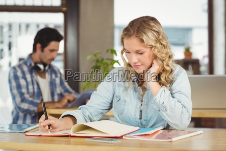 businesswoman writing in book while working