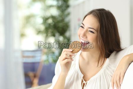 happy girl eating a dietetic cookie