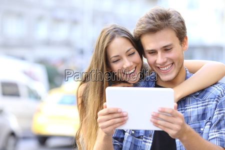 happy couple sharing a tablet in