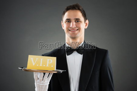 happy waiter holding tray with vip