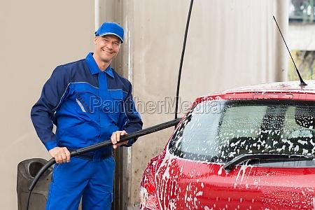 zuversichtlich male worker washing red wagen