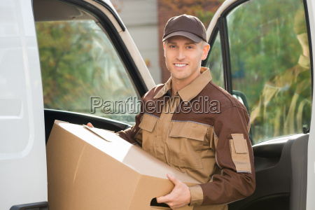 young delivery man removing cardboard box