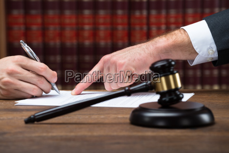 judge assisting client to sign legal