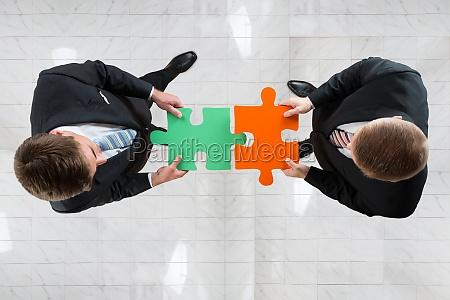 businessmen assembling jigsaw puzzle representing teamwork