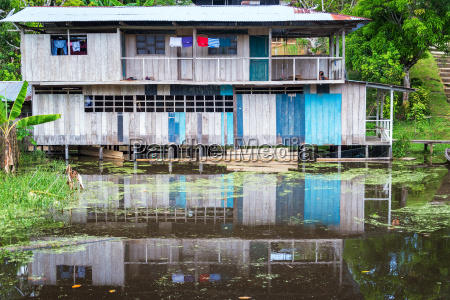 house reflected in amazon river