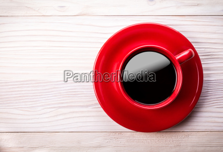 red coffee cup on light wooden