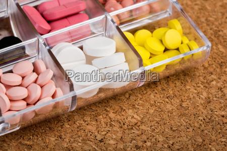 verschiedene pillen im plastikbehaelter