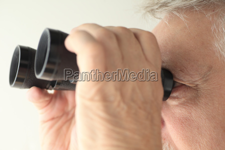 binoculars held by senior man