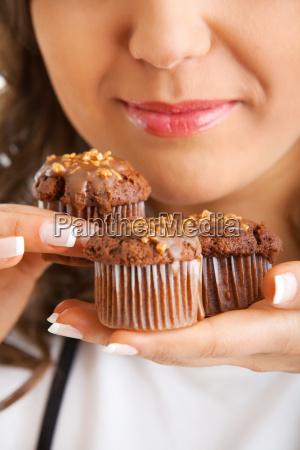 junge frau isst schokolade muffin junge