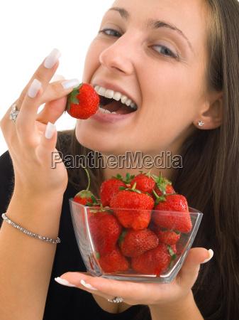 junge frau isst erdbeeren junge frau