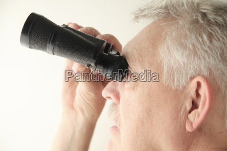 man with binoculars looks up