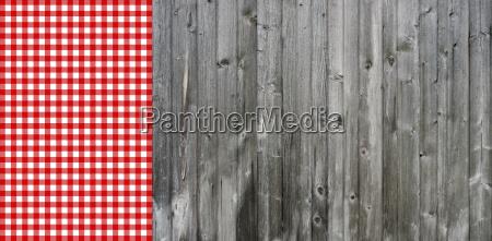 graue holzbretter mit tischdecke rot weiss
