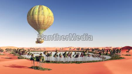fantasie heissluftballon ueber einer wuestenoase