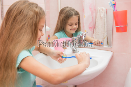 girl rinse the toothbrush under running