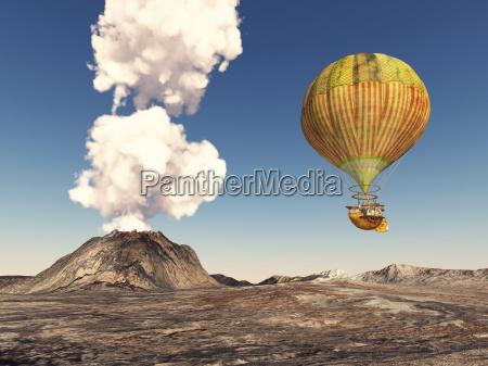 fantasie heissluftballon ueber einer vulkanlandschaft