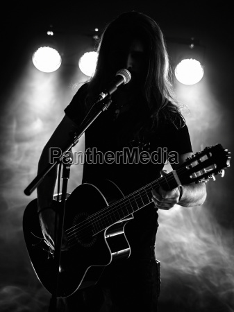 silhouette acoustic guitar player on stage