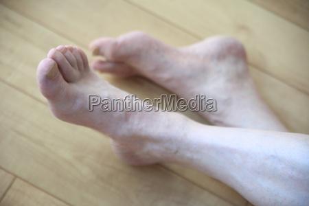 senior man crosses legs on floor