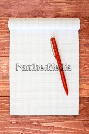 notebook and red pen on the