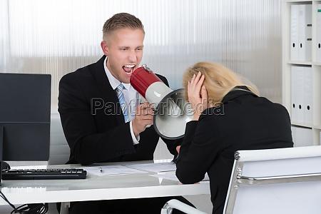 boss shouting at businesswoman through loudspeaker
