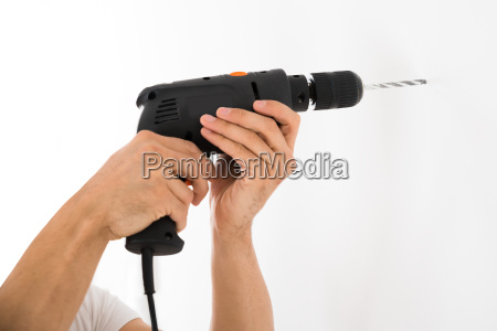 man using power drill on white