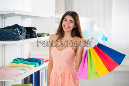 smiling woman carrying colorful shopping bags
