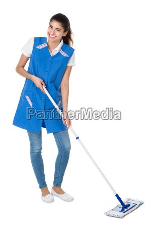 happy female janitor mopping on white