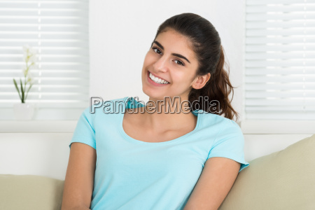 happy woman sitting on sofa at