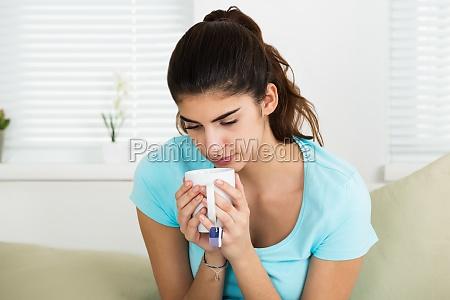 sick woman holding tee mug at