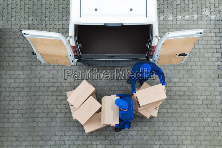 delivery men unloading cardboard boxes from