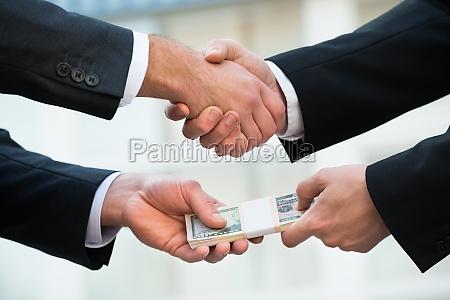 businessman shaking hand while bribing partner