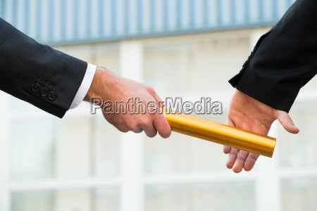 businessman passing relay baton to colleague