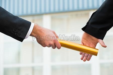 geschaeftsmann uebergibt staffel baton zu kollegen