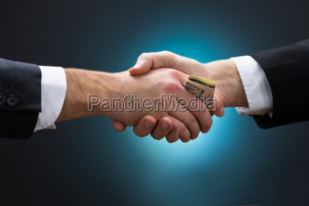 businessman shaking hands while giving bribe