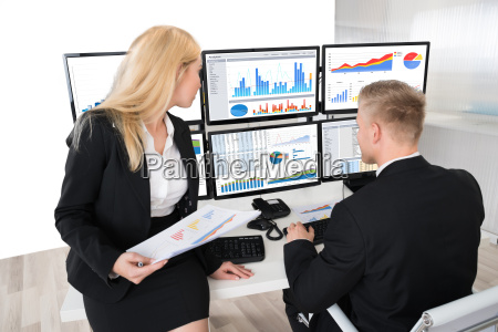 financial workers analyzing graphs on computers