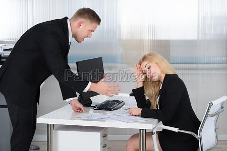 boss shouting at mitarbeiter am schreibtisch