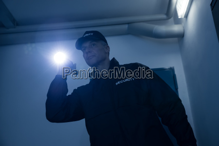 security guard searching with flashlight in