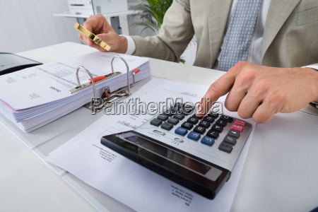 accountant using calculator while holding magnifying