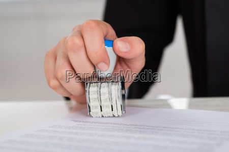 businesswoman stamping contract paper at desk
