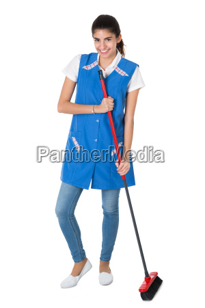 happy female janitor sweeping on white