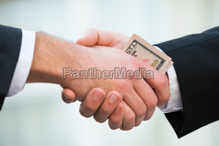 businessman bribing partner while shaking hand