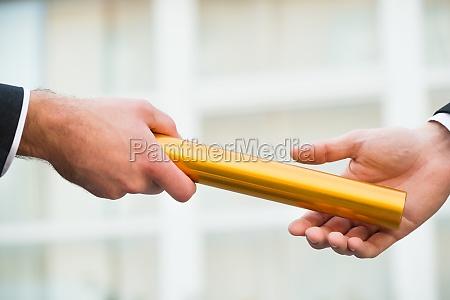 businessman giving relay baton to colleague