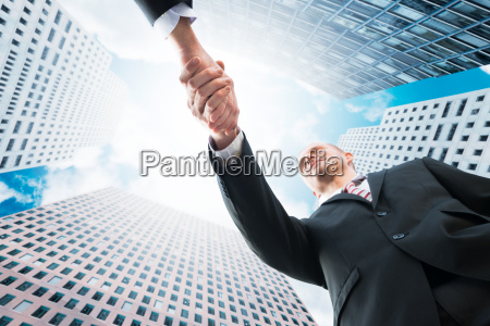 businessman shaking hand with partner against