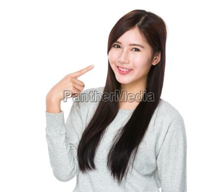 asiatische junge frau mit fingerpunkt zu