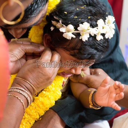traditionelle indische hindu familie ohr piercing