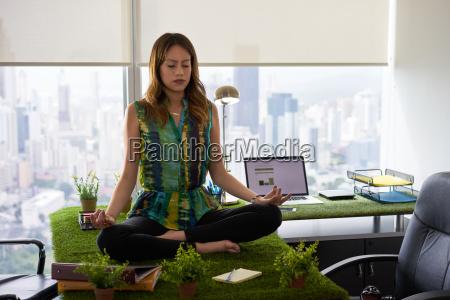 geschaeftsfrau tun yoga meditation auf dem