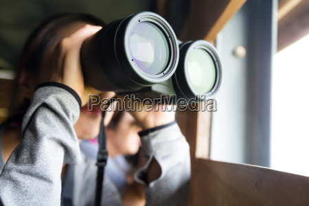 asian woman use of the binoculars