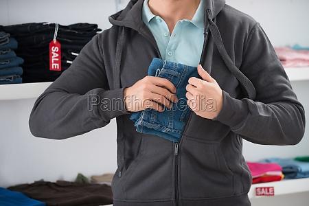 man versteckt jeans in der jacke