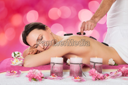 relaxed woman receiving hot stone therapy